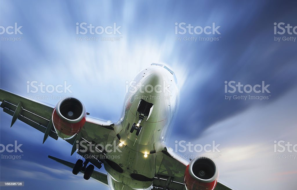 Sunlit airplane taking off against dramatic sky stock photo