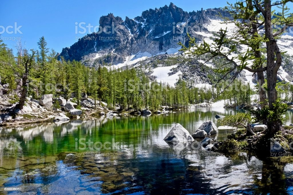 Sunlit alpine forest, clear lake and granite mountain. stock photo