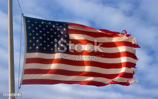 istock Sunlit American Flag On Background Of Clouds 1219018781