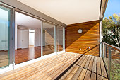 sunlit balcony with wooden floor and wall of an architectural contemporarily apartment building in green area.