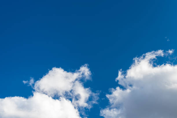 Sunlit blue sky background with copy space and group of white precipitation clouds stock photo