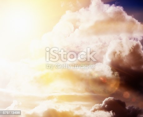 istock Sunlit cloudscape: sun breaking dramatically through storm clouds 579773498