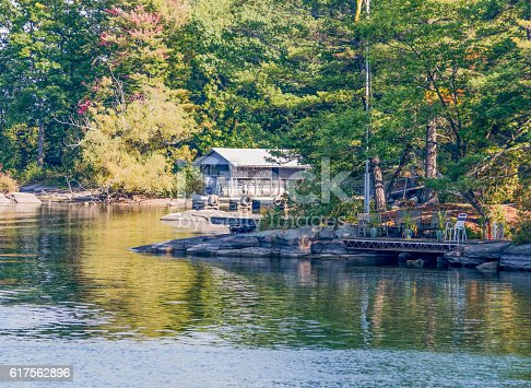 istock Sunlit Cottage on a River's bay 617562896