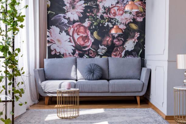 sonnendurchflutete, grau sofa mit einer floralen print mauer im winkel eine feminine wohnzimmer interieur mit goldenen accessoires - blumendrucktapete stock-fotos und bilder