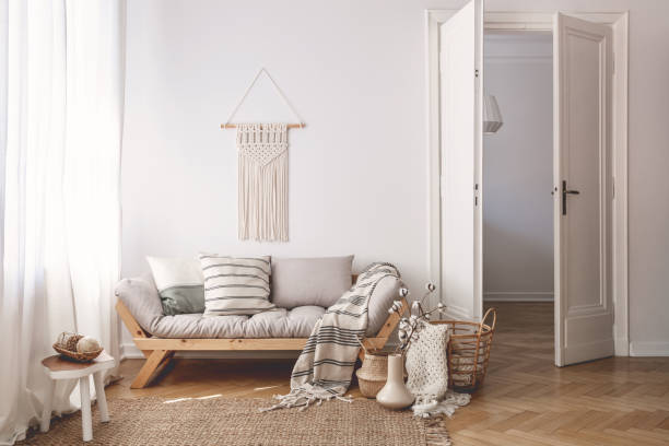 Sunlit living room interior with open door, herringbone parquet floor, natural, beige textiles and white walls stock photo