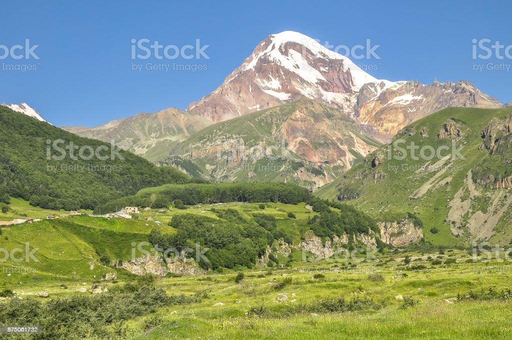 Sunlit mountain Kazbek on blue sky background stock photo