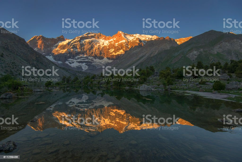 Sunlit mountain reflecting in lake stock photo