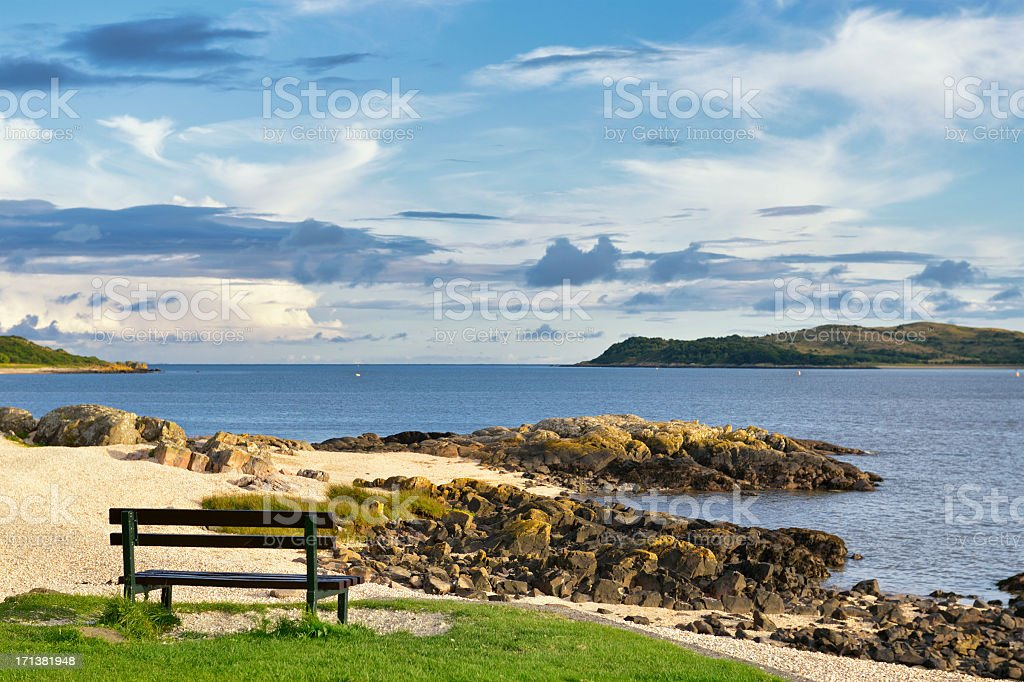 Sunlit Scottish coastal scene with blue sky and white clouds stock photo