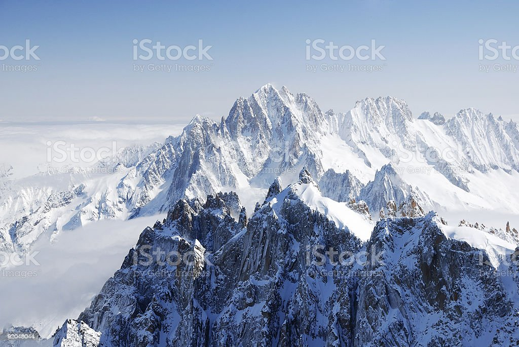 Sunlit snow peaks among white cloudy fields, the Alps stock photo