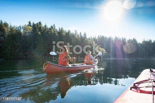 Multi-ethnic women (mature mother and teen daughter) ocean canoeing in rural Bamfield, Vancouver Island, British Columbia, Canada.