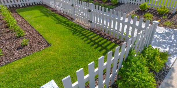 zonovergoten tuin met gazon witte hek en struiken - hek stockfoto's en -beelden