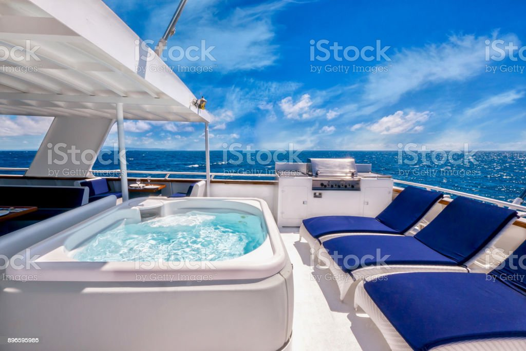 Sunny aft deck of large private motor yacht featuring a hot tub spa, deck chairs and a barbecue grill, in a tropical location, adding to the concept of living the good life. stock photo
