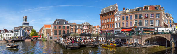 Sunny afternoon in Leiden The Aalmarkt in the old city of Leiden on a sunny afternoon; terraces mounted on barges floating on the canal, are busy with people. In the background left the neoclassical Hartebrug church (1836), and the newly constructed Catharina footbridge (2016), the longest Ultra High Performance Concrete bridge in the Nethrlands leiden stock pictures, royalty-free photos & images