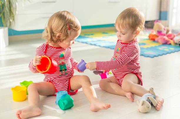 sonnige wohnung die niedlichen zwillinge sitzt barfuß auf dem boden - 2 3 jahre stock-fotos und bilder