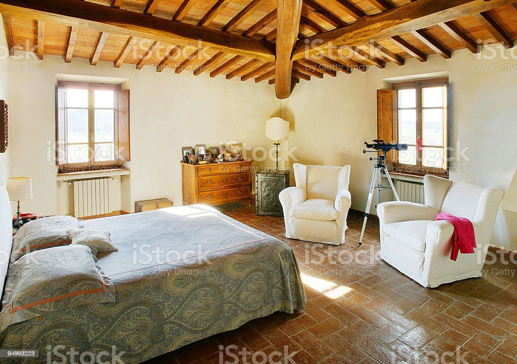 Sunny bed-room with raftered ceiling in a beautiful rustical house stock photo