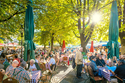 Munich, Germany - September 29, 2016: Viktualienmarkt beer garden is located at Munich's central food market. People sitting at the wooden tables and enjoying the sunny weather. They are drinking Beer and eating traditional Bavarian meals.