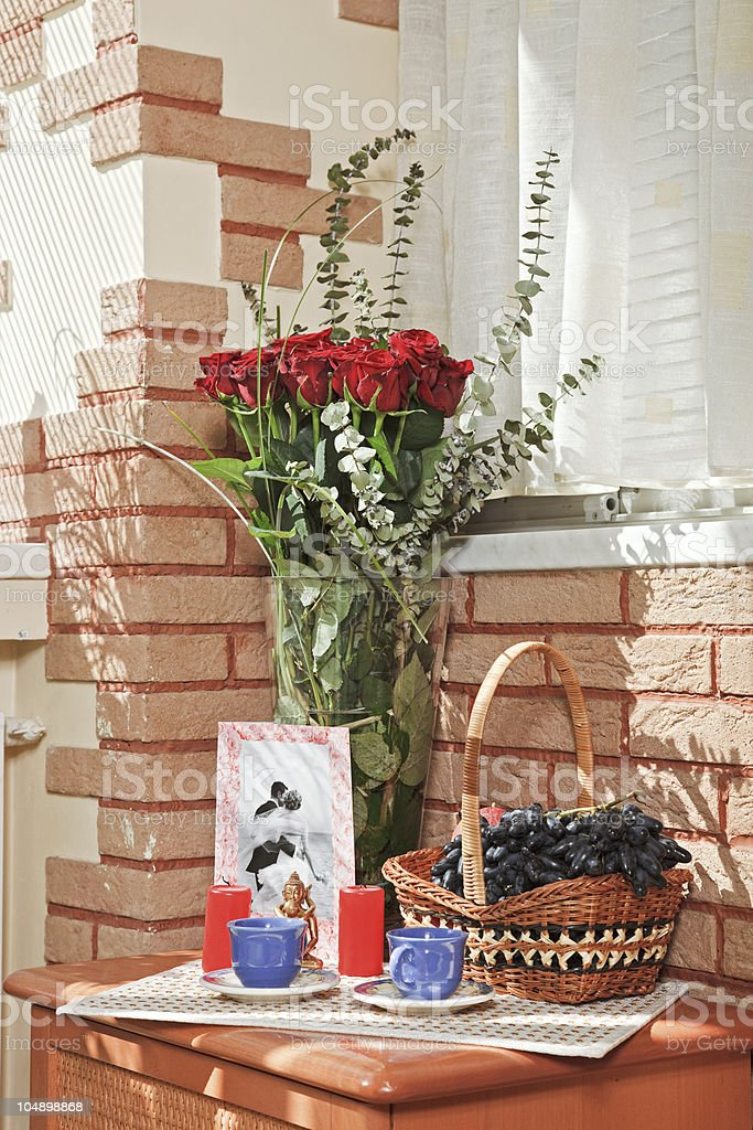 Sunny composition with rose bouquet and fruit basket royalty-free stock photo