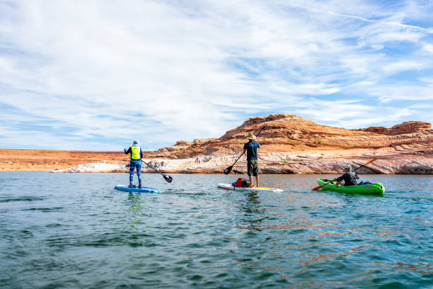 Sunny day at Lake Powell with group of people doing stand up paddle boarding boats Page, USA - August 9, 2019: Sunny day at Lake Powell with group of people doing stand up paddle boarding boats and view of canyons water lake powell stock pictures, royalty-free photos & images