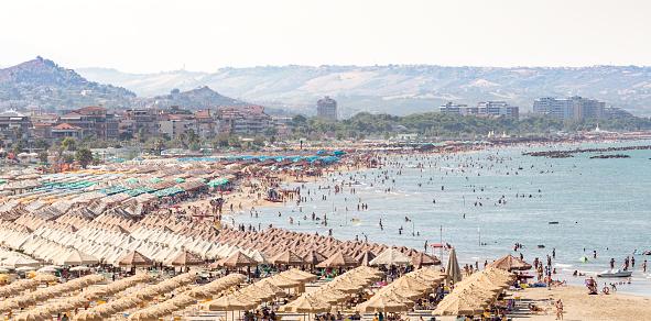 Sunny day atr beach of Pescara. Huge beach full of people and parasols, Abruzzo, Italy