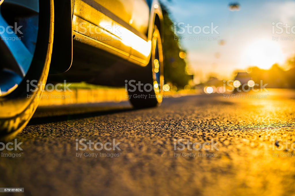 Sunny day in a city, headlights of approaching car stock photo