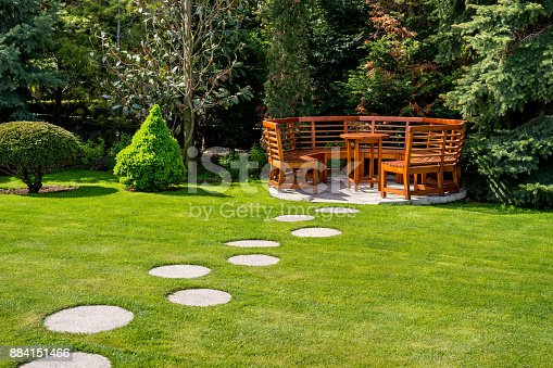 istock Sunny day in a spring garden with wooden benches 884151466