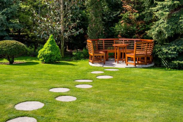 dia de sol em um jardim de primavera com bancos de madeira - banco assento - fotografias e filmes do acervo