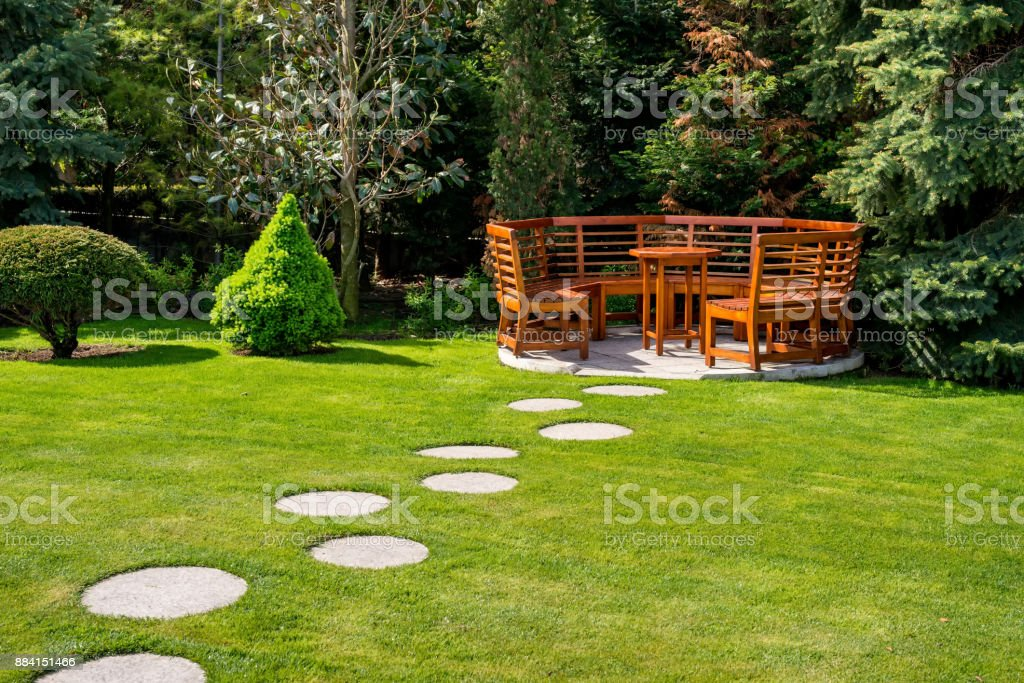 Sunny day in a spring garden with wooden benches stock photo