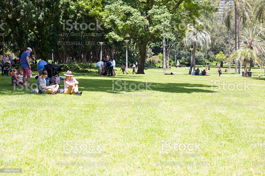 Sunny day in city park with people relaxing on grass stock photo