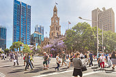People walking in George St on a sunny day with the Sydney Town Hall building in the background.