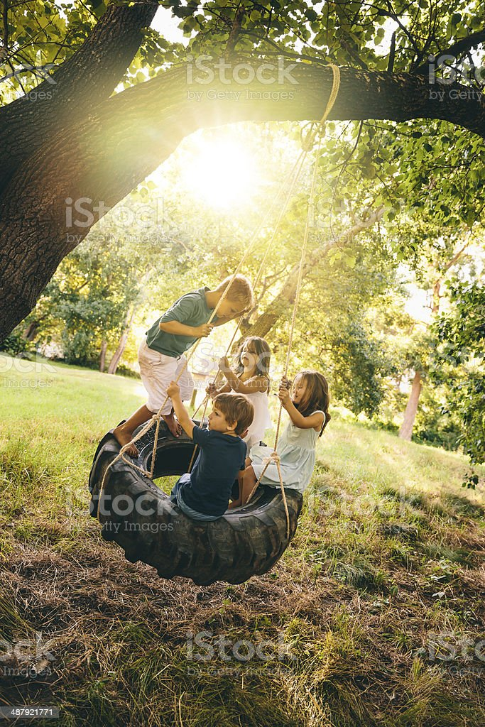 Sunny day kids swinging stock photo