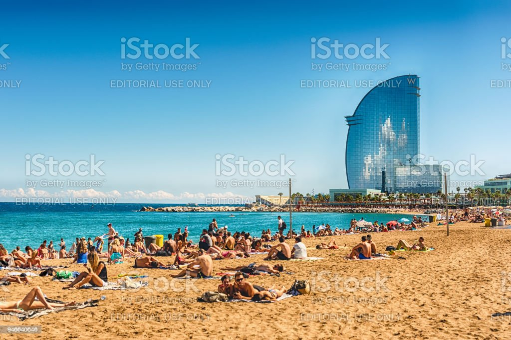 A sunny day on the Barceloneta beach, Barcelona, Catalonia, Spain BARCELONA - AUGUST 10: People enjoying a sunny day on La Barceloneta beach, Barcelona, Catalonia, Spain, on August 10, 2017 Barcelona - Spain Stock Photo