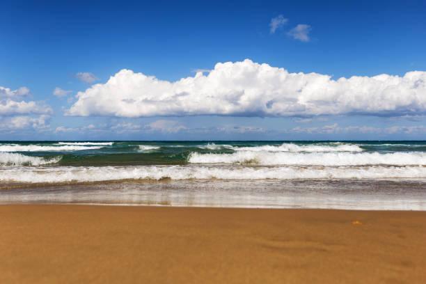 sonnigen tag am strand mit großen wellen und weißen wolken - roll tide stock-fotos und bilder