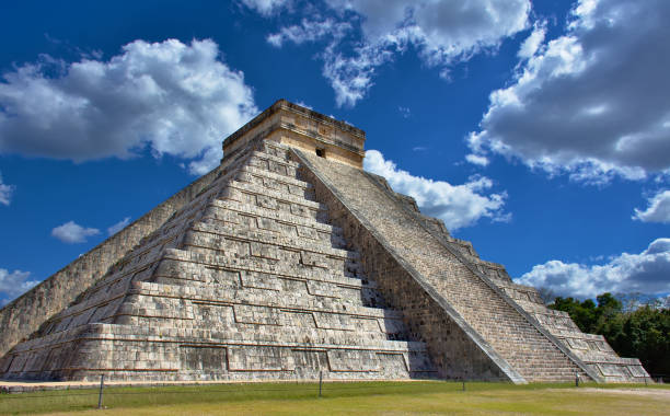 Sunny day with blue sky and white clouds. No people around. El Castillo (The Kukulkan Temple) of Chichen Itza, mayan pyramid in Yucatan, Mexico - Mar 2, 2018 stock photo