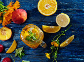 Cold iced drink with fresh orange, lemon, peach, plum and grapefruit on the blue wooden table. Overhead view