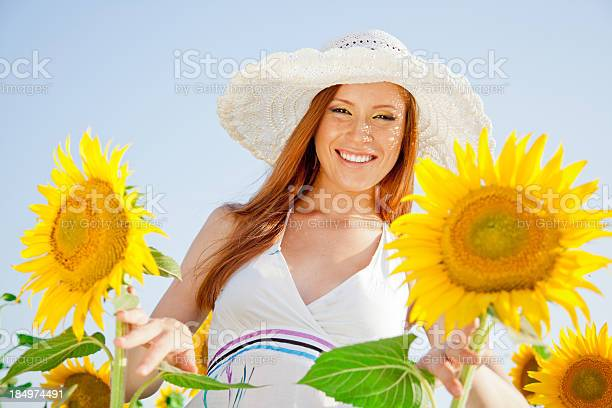 Photo of Sunny, full of life, young woman portrait with sunflowers