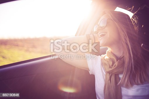 Woman sitting on the passenger's seat in the car and having fun on the road trip on a sunny day
