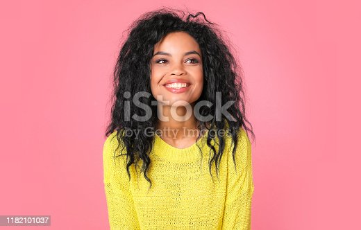 857924506 istock photo Sunny girl. Beautiful tanned woman with Afro hairstyle is laughing while posing in a knitted light yellow sweater, looking to the right and smiling at the camera. 1182101037