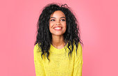 istock Sunny girl. Beautiful tanned woman with Afro hairstyle is laughing while posing in a knitted light yellow sweater, looking to the right and smiling at the camera. 1182101037