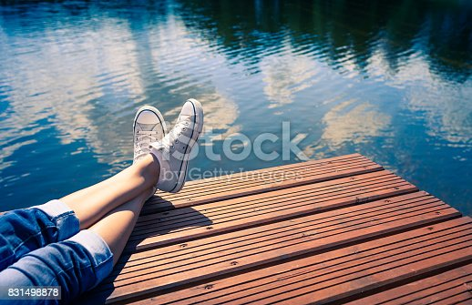 Woman relaxes by the lake sitting on the edge of a wooden jetty , swing one's feet near the water surface. Sunny joyful summer day concept.