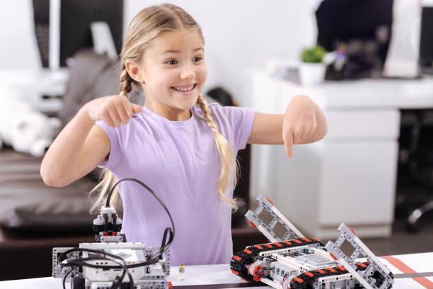 sonnige kleine mädchen, die erforschung neuer technologien in der schule - lernfortschrittskontrolle stock-fotos und bilder