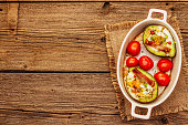 Sunny morning breakfast. Baked eggs in avocado half, bacon, tomato cherry, spices. Healthy food, ketogenic diet concept. Old wooden boards background