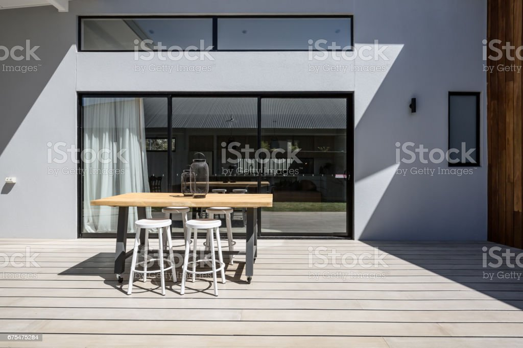 Sunny outdoor entertaining deck with triple glass sliding doors stock photo