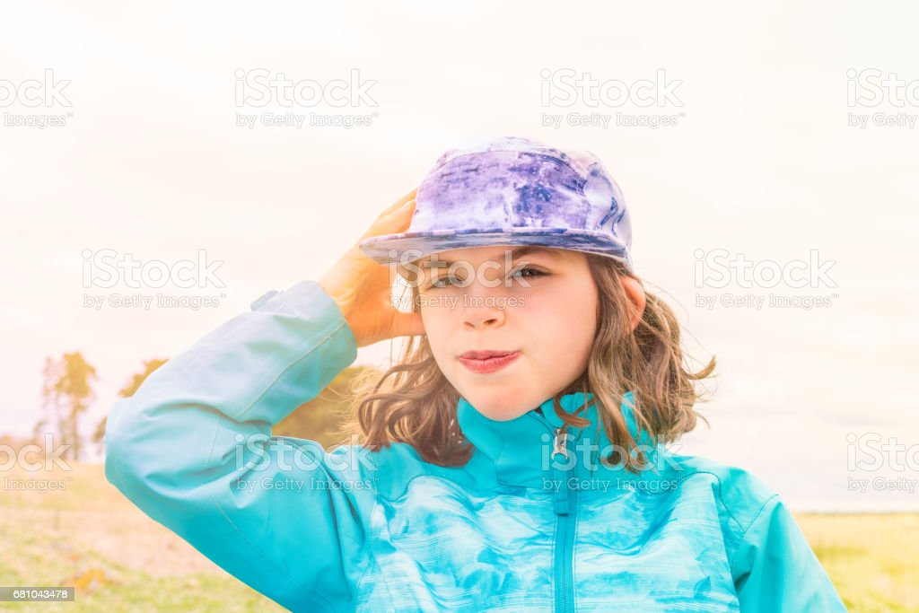 Sunny portrait of cute caucasian girl in blue jacket and cap with wind in her hair. royalty-free stock photo