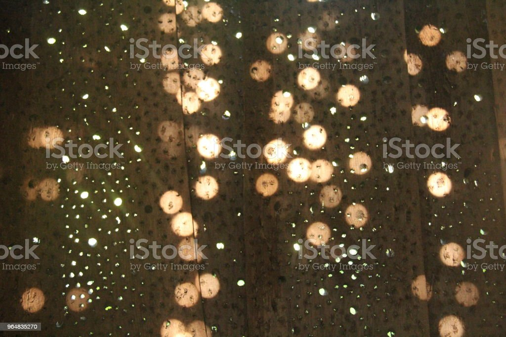 Sunny round glare from the sun on a wooden wall. Sunny background, yellow sunny circles on the wall. royalty-free stock photo