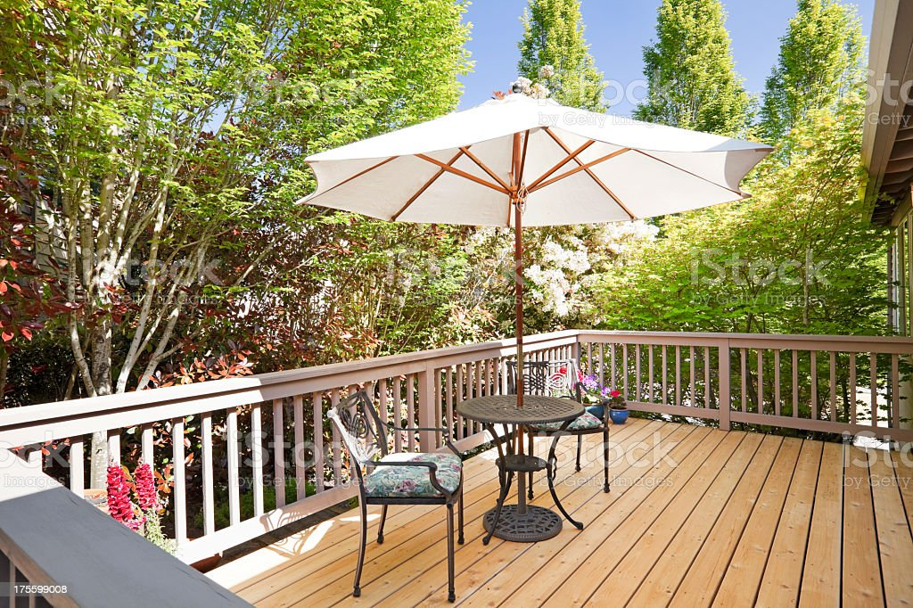 Sunny second floor back deck with breakfast table stock photo