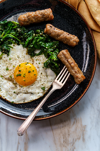Fried sunny side up American egg breakfast with sausage and sauteed spinach