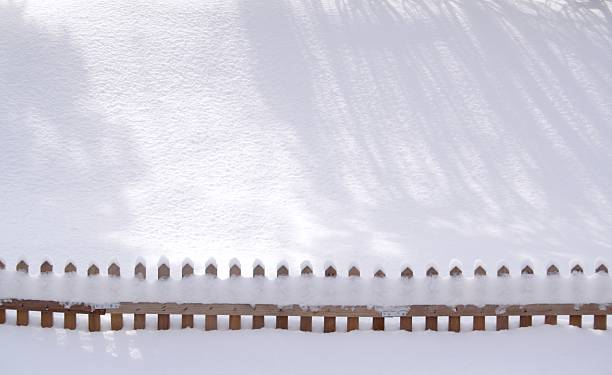 Sunny Snow Shadows and a Fence stock photo