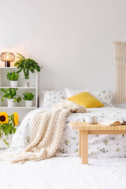 sonnigen frühlingstagen schlafzimmer innenraum mit grünpflanzen neben einem bett in öko-baumwoll-leinen gekleidet. gelben akzenten. leere weiße hintergrundwand. echtes foto. - teppich baumwolle stock-fotos und bilder