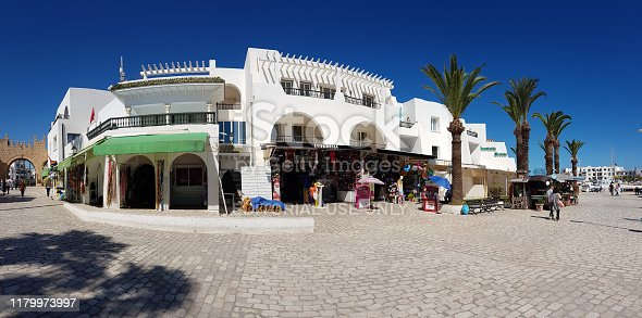 Several tourists are in the quiet street with touristic shops of Tunisian town Hammam Susa.