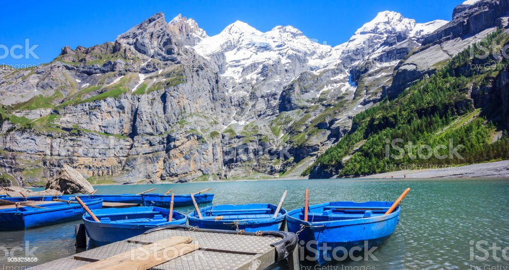 Sunny Summer Activities and recreation, rowing blue boats while enjoying beautiful Swiss alps view on Lake Oeschinen (Oeschinensee), near Kandersteg, Bernese Oberland, Switzerland, Europe stock photo